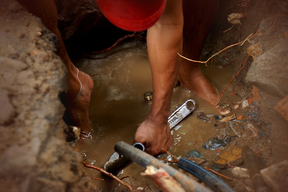 Plumber with tools repairing an underground water leak